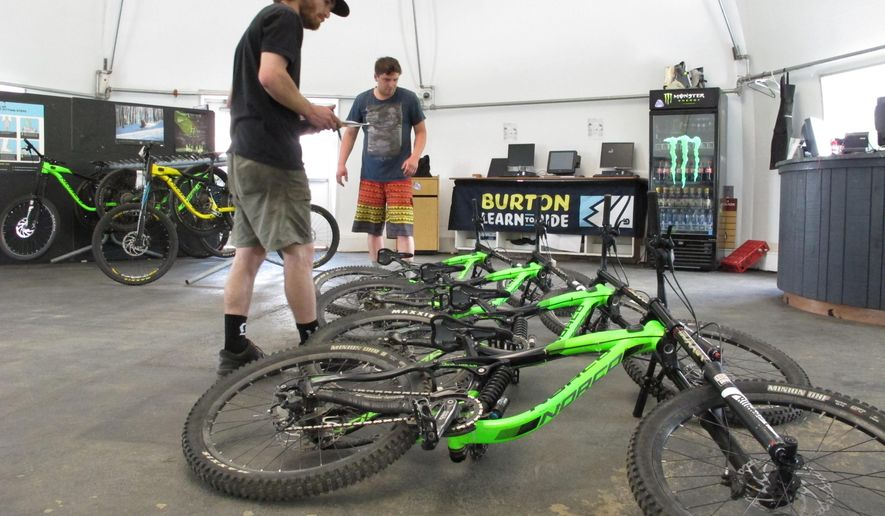 In this June 1, 2016 photo, Ry Wolfel, a bike mechanic with East Burke Sports inspects rental bikes in East Burke, Vt. Burke Mountain Resort has reopened for the mountain biking season after its owner was accused of fraud. (AP Photo/Lisa Rathke)