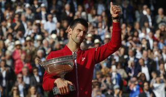 Serbia's Novak Djokovic gives a thumbs up as he holds the trophy after winning the final of the French Open tennis tournament against Britain's Andy Murray in four sets 3-6, 6-1, 6-2, 6-4, at the Roland Garros stadium in Paris, France, Sunday, June 5, 2016. (AP Photo/Michel Euler)