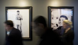 Photos of Muhammad Ali hang on the wall as people pass by before the start of a press conference regarding the funeral for Ali at the Muhammad Ali Center, Monday, June 6, 2016, in Louisville, Ky. The president of Turkey and king of Jordan joined the long line of world leaders, religious figures and superstars set to speak at Ali's funeral Friday. (AP Photo/David Goldman)