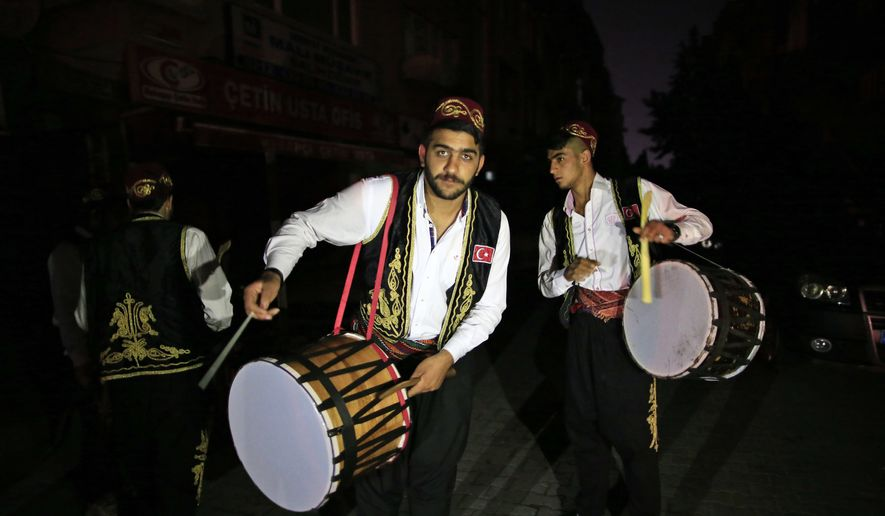 """On the first day of the Muslim holy month of Ramadan, drummers, wearing traditional Ottoman clothes, perform through the neighborhoods of Istanbul, early Monday June 6, 2016, to wake people for the """"sahour,"""" the traditional breakfast of Ramadan. More than 2000 drummers wander Istanbul's neighborhoods playing their drums in the early hours to wake up the residents as part of the holiday tradition. (AP Photo/Lefteris Pitarakis)"""