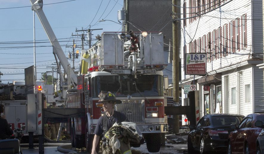 A fire fighter contains a fire at an apartment Monday, June 6, 2016, in Manchester, N.H. Firefighters say a blaze in an apartment building in Manchester, New Hampshire, has left four people dead. (AP Photo/Jim Cole)