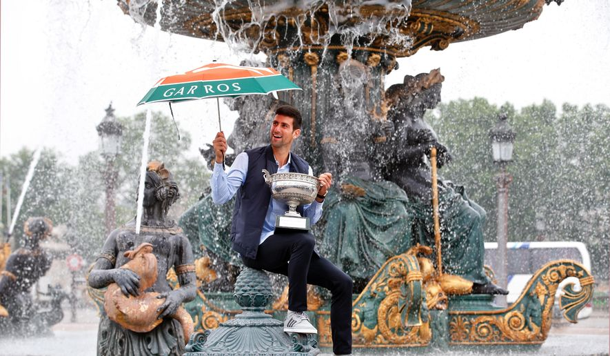 Novak Djokovic, from Serbia, poses with the French Open tennis trophy during a photo session at the Place de la Concorde, in Paris, Monday June 6, 2016. Djokovic was the winner against Britain's Andy Murray in four sets 3-6, 6-1, 6-2, 6-4. (AP Photo/Thibault Camus)