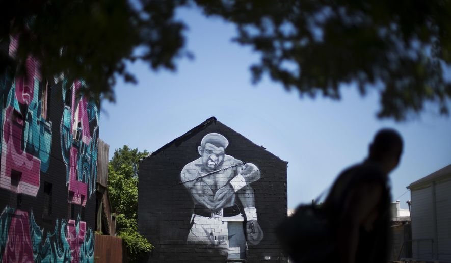 A pedestrian passes a mural of Muhammad Ali painted on the side of a building Monday, June 6, 2016, in Louisville, Ky. The president of Turkey and king of Jordan joined the long line of world leaders, religious figures and superstars set to speak at Ali's funeral Friday. (AP Photo/David Goldman)