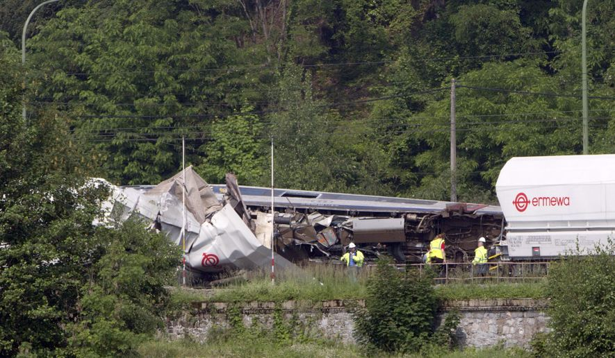 Investigators stand near the wreckage of a train after it crashed in Hermalle-sous-Huy, near Liege, Belgium, Monday, June 6, 2016. A late-night passenger train slammed into the rear of a halted freight train in eastern Belgium, derailing two cars, authorities said Monday. (AP Photo/Virginia Mayo)