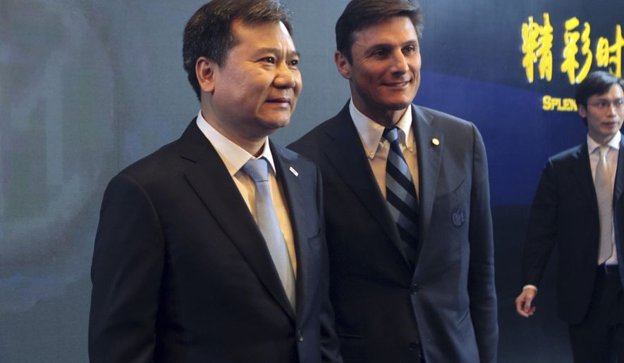 Javier Zanetti, right, former captain of Inter Milan, and Zhang Jindong, chairman of Suning Group, pose for photos during a presser in Nanjing in eastern China's Jiangsu province Monday, June 6, 2016. The Chinese retail giant announced taking a majority stake in the Italian soccer club. (Chinatopix Via AP) CHINA OUT