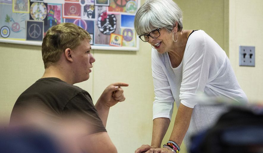 In this May 6, 2016, photo, Ann Young, a special education teacher at Auburn High School, answers a question from Chris Clark during a math exam at the school in Auburn, Ill. Young is retiring from the school district after 33 years, including 26 as a special education teacher at the school. (Justin L. Fowler/The State Journal-Register via AP) NO SALES, MANDATORY CREDIT
