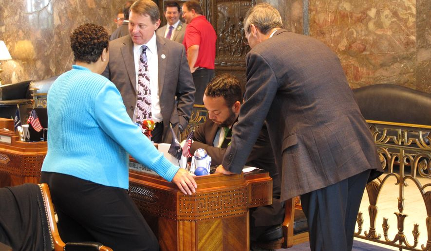 Senators huddle around the desk of Revenue and Fiscal Affairs Chairman J.P. Morrell, D-New Orleans, on the final day of the regular legislative session, on Monday, June 6, 2016, in Baton Rouge, La. Morrell is the lead Senate negotiator on the construction budget, which was one of the bills tied up in last-minute haggling. (AP Photo/Melinda Deslatte)