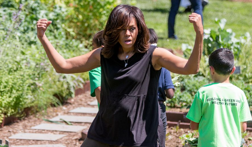 First lady Michelle Obama, joined by school children from across the country, jokingly flexes her muscles for members of the media as she harvests the White House Kitchen Garden, Monday, June 6, 2016, at the White House in Washington. (AP Photo/Andrew Harnik)