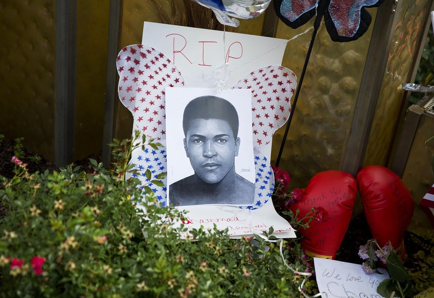 An image of Muhammad Ali and boxing gloves are left at a makeshift memorial to Ali at the Muhammad Ali Center, Monday, June 6, 2016, in Louisville, Ky. The president of Turkey and king of Jordan joined the long line of world leaders, religious figures and superstars set to speak at Ali's funeral Friday. (AP Photo/David Goldman)
