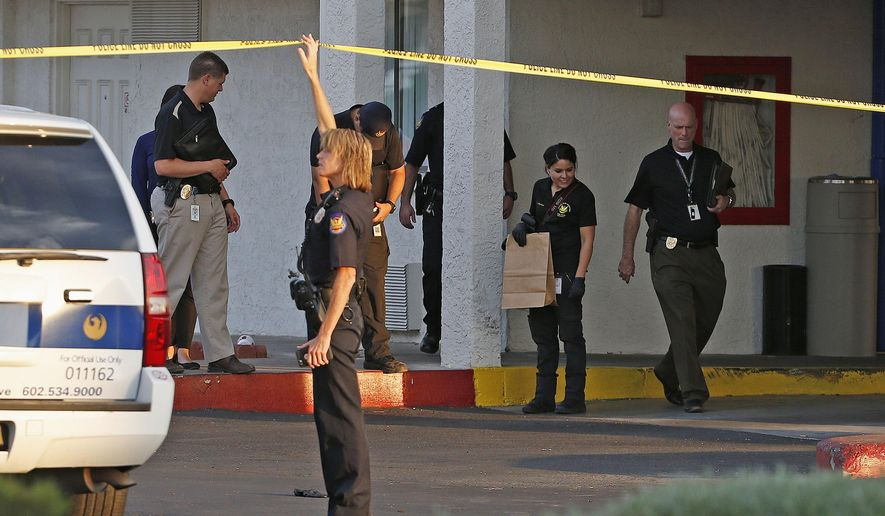 Phoenix Police Department officers and investigators comb the area for evidence at a local motel where multiple people were shot, some fatally, early Monday, June 6, 2016, in Phoenix. (AP Photo/Ross D. Franklin)