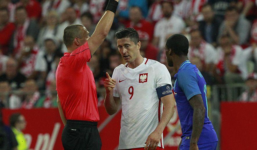Czech referee Miroslav Zelinka, left, gives a yellow card to Robert Lewandowski, center, of Poland during a friendly soccer match between Poland and Netherlands in Gdansk, Poland, Wednesday, June 1, 2016. (AP Photo/Czarek Sokolowski)