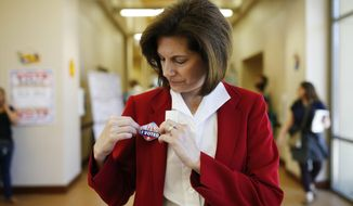 In this May 31, 2016, photo, U.S. Senate candidate Catherine Cortez Masto applies a sticker to her jacket after voting at an early voting site in Las Vegas. A former state attorney general, Masto, would be the first Latina ever to serve in the U.S. Senate. (AP Photo/John Locher)