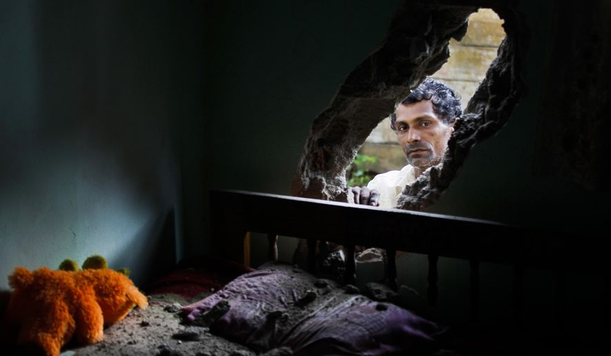 A Sri Lankan man peeps into his bedroom through a hole caused by an artillery explosion during a fire at a military base in Salawa, about 35 kilometres (22 miles) east of Colombo, Sri Lanka, Monday, June 6, 2016. Minister of Law and Order Sagala Ratnayake said the fire started at a small arms depot and then spread to other depots where heavy weapons, such as artillery shells, were stored. (AP Photo/Eranga Jayawardena)