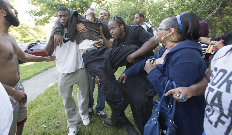 A man who rushed towards the taped off crime scene, is helped after he became faint, eventually being checked by medical personnel on the scene of three fatal shootings at a house in the 6500 block of Brace in Detroit, Mich., on Monday, June 6, 2016. Police say three young men are dead following a shooting at a suspected drug house in Detroit.  (Daniel Mears/The Detroit News via AP)