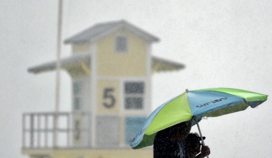 Beachgoers take shelter under an umbrella after a sudden downpour associated with tropical storm Colin came ashore at Clearwater Beach Monday, June 6, 2016, in Clearwater, Fla. Colin was expected to make landfall somewhere along Florida's gulf coast. (AP Photo/Chris O'Meara)