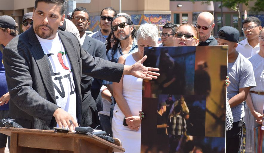 """Javier Benavidez, executive director of the advocacy group Southwest Organizing Project, speaks at a press conference in Albuquerque, Monday, June 6, 2016. Benavidez is pointing to images of an Albuquerque anti-Donald Trump protest last month that he says showed authorities overreacted against demonstrators. Albuquerque police are continuing to search for suspects linked to the violent protest while advocates say the effort is part of a """"well-financed witch hunt."""" (AP Photo/Russell Contreras)"""