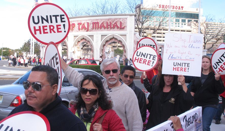 This Oct. 24, 2014 photo shows casino workers picketing the Trump Taj Mahal Casino in Atlantic City, N.J, a week after a bankruptcy judge terminated unionized workers' health insurance and pension benefits. A survey released Monday June 6, 2016 by Local 54 of the Unite-HERE union shows 33 percent of Taj Mahal casino workers have no health coverage at all, while another 50 percent rely on coverage under the taxpayer-subsidized Affordable Care Act. (AP Photo/Wayne Parry)
