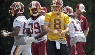 Washington Redskins quarterback Kirk Cousins (8) claps as he breaks the huddle during practice at the team's NFL football training facility at Redskins Park, Wednesday, June 1, 2016 in Ashburn, Va. (AP Photo/Alex Brandon)