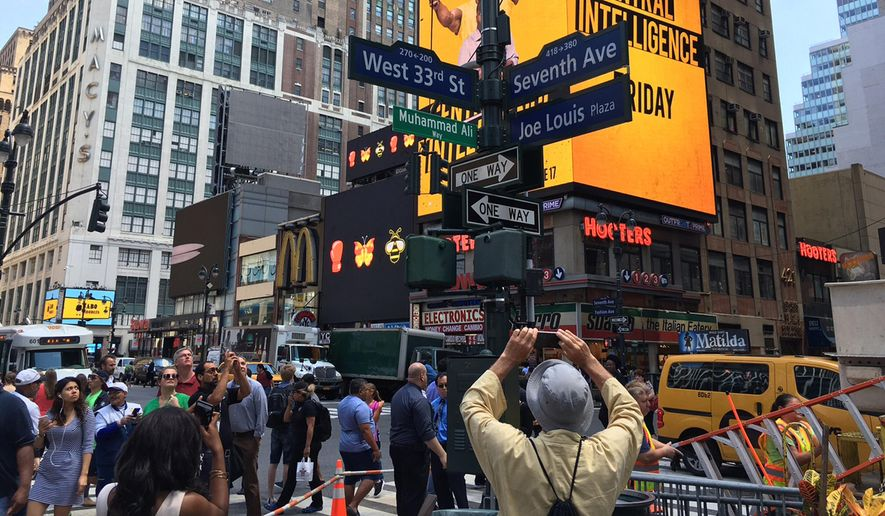 """In this photo provided by New York City Hall, pedestrians photograph a street sign renaming West 33rd Street between 7th and 8th Avenues, """"Muhammad Ali Way,""""  Tuesday, June 7, 2016, in New York. Mayor Bill de Blasio announced the length of street next to New York's Madison Square Garden will be temporarily renamed to honor the boxing legend who had fought in the famed arena, and died last week. (Michael Appleton/Mayoral Photography Office via AP)"""