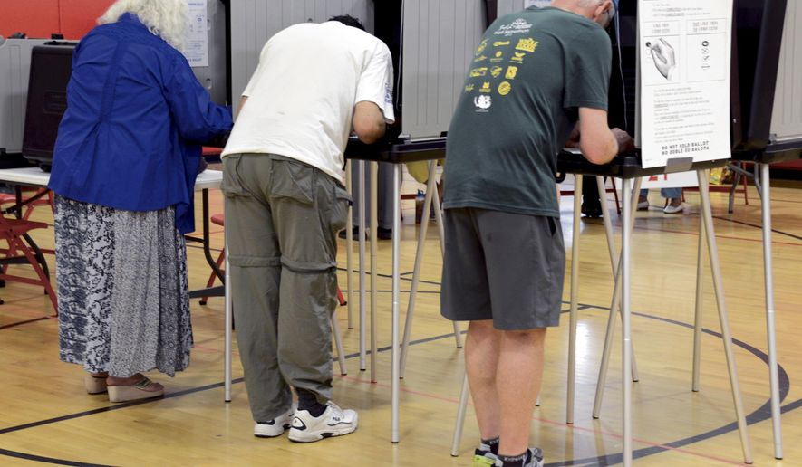 Voters fill out their ballots during the New Mexico Primary Election at Gonzales Community School in Santa Fe, on Tuesday, June 7, 2016. New Mexico voters will get an unusually decisive say Tuesday in the final round of state presidential primaries in which Hillary Clinton is on track to clinch the majority of Democratic delegates nationwide.  (Clyde Mueller/Santa Fe New Mexican via AP) MANDATORY CREDIT