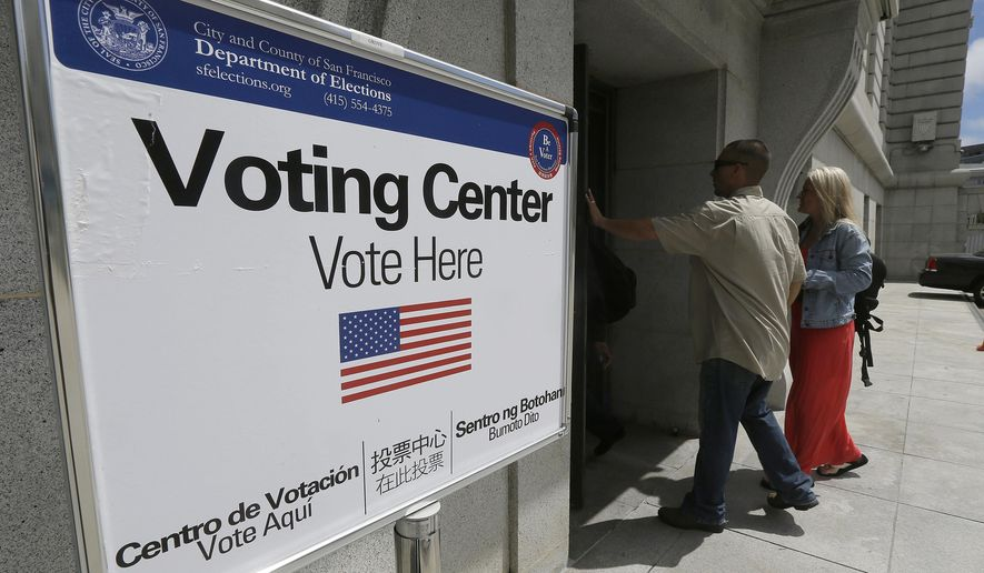 FILE - In this Tuesday, June 7, 2016 file photo, a man and woman walk past a Department of Elections sign while entering City Hall in San Francisco. Voter turnout in California's primary looked about average, despite a last-minute surge in registration and intense interest in an unusually competitive presidential contest. Ballots counted by Wednesday morning, June 8, represented only one in four eligible Californians and one in three registered voters. (AP Photo/Jeff Chiu, File)