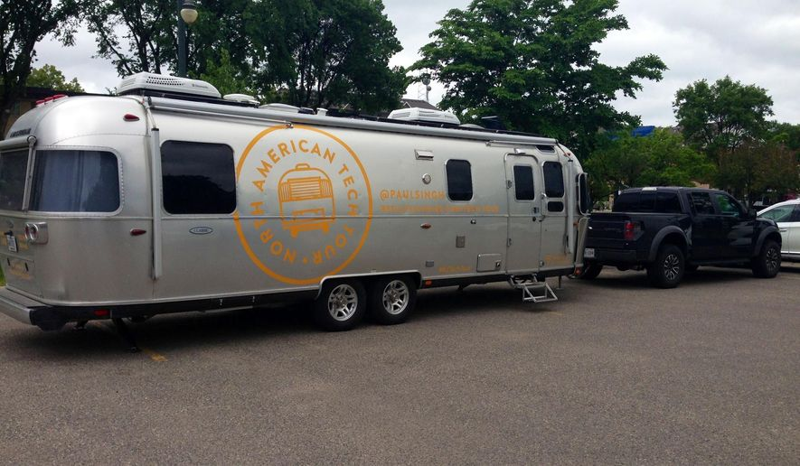Washington, D.C.-based venture capitalist Paul Singh is traveling the United States and Canada in this Airstream travel trailer, shown outside a park in Fargo, N.D., on Tuesday, June 2, 2016. Singh is on a 34-city tour talking to startup company founders and meeting with investors. The trailer has a hybrid computer system, solar array, high-powered electrical system, air ducts, and water tank to last seven days. (AP Photo/Dave Kolpack)