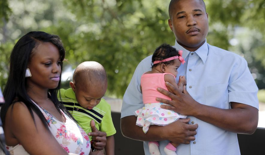 Isaiah Baskins, right, holds his daughter Ka'leigh Baskins, as his wife Whitnee Watkins, left, holds their son Caleb Baskins, 21 months, during a news conference in Winston-Salem, N.C., Wednesday, June 8, 2016. Isaiah Baskins and Katie Thomas were subjected to a racial rant by a volunteer at the Wake Forest Baptist Medical Center that Baskins recorded. Attorney Justin Bamberg, representing the family of Isaiah Baskins, says he's negotiating with the hospital to ensure such incidents aren't repeated.   (AP Photo/Chuck Burton)