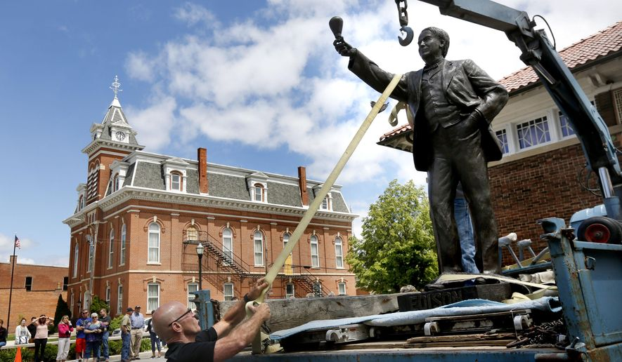 Sculpture Alan Cottrill helps remove his 900-pound statue of Thomas Edison from a flatbed truck, during a  celebration Tuesday, June 7, 2016, in Edison's hometown of Milan, Ohio.  More than 50 people turned out to watch a short parade of the statue, which wound its way through downtown and stopped off at Edison's childhood home before ended at the Milan-Berlin Public Library in downtown Milan. The statue will be on display inside the library until September, when it will be shipped to Washington D.C. to represent Ohio in the National Statuary Hall.   (Katie Rausch/The Blade via AP)  MANDATORY CREDIT; MAGS OUT; NO SALES; TV OUT; SENTINEL-TRIBUNE OUT; MONROE EVENING NEWS OUT; TOLEDO FREE PRESS OUT