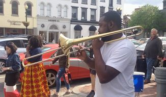Travis Gardner, 32, of the Brass Connection Band plays to a crowded Georgetown street. By Faith E. Pinho/The Washington Times