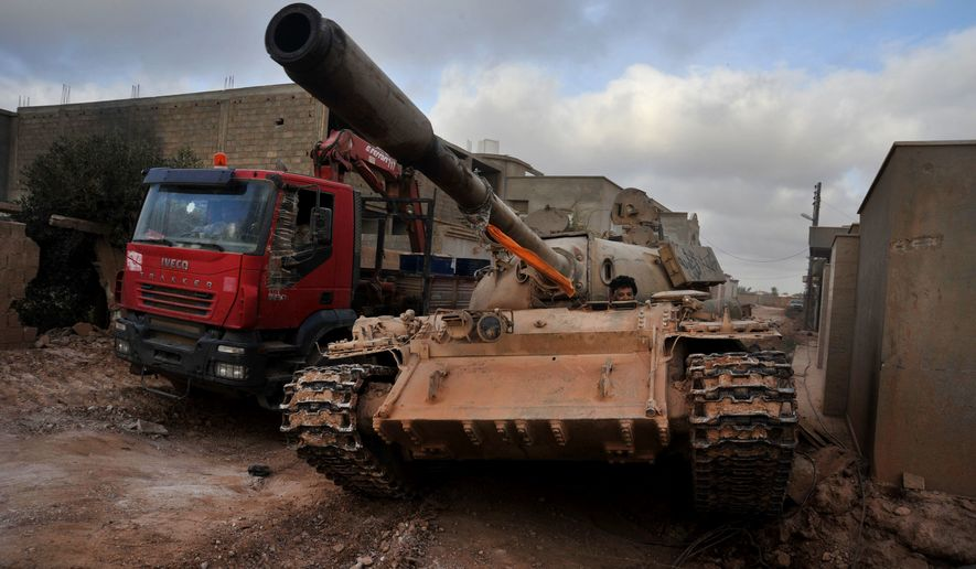 A man loyal to the Libyan armed forces sits in a tank during clashes with Islamic State group militants west of Benghazi, Libya. Islamic State militants are fleeing their main bastion in Libya, a day after militiamen loyal to a U.N.-brokered government pushed into the central city of Sirte. (AP Photo/Mohammed el-Shaiky, File)