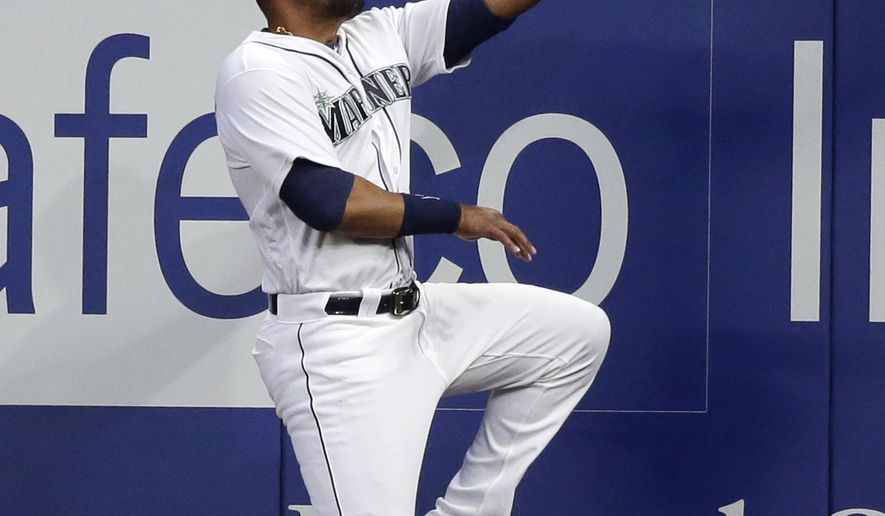Seattle Mariners right fielder Franklin Gutierrez leaps on the run to catch a fly ball from Cleveland Indians' Juan Uribe against the wall during the seventh inning of a baseball game Wednesday, June 8, 2016, in Seattle. (AP Photo/Elaine Thompson)