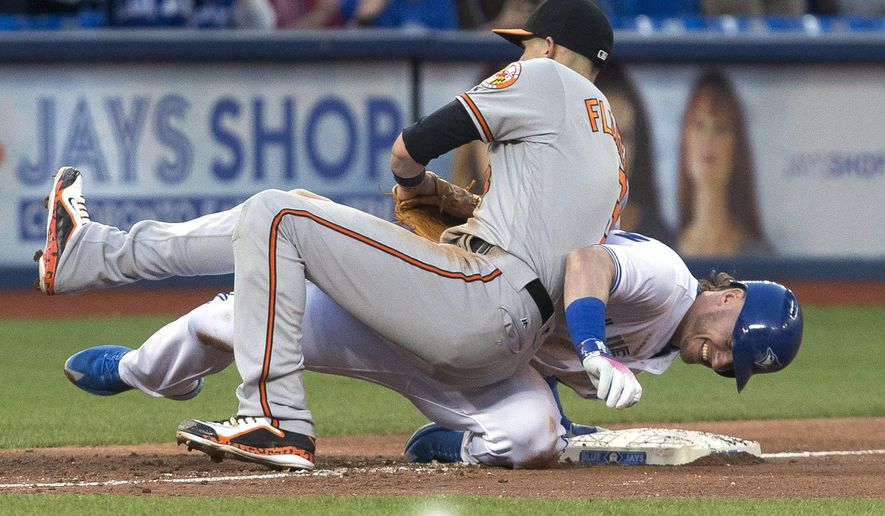 Toronto Blue Jays third baseman Josh Donaldson, right, collides with Baltimore Orioles third baseman Ryan Flaherty after hitting an RBI triple during the fourth inning of a baseball game Thursday, June 9, 2016, in Toronto. (Chris Young/The Canadian Press via AP)