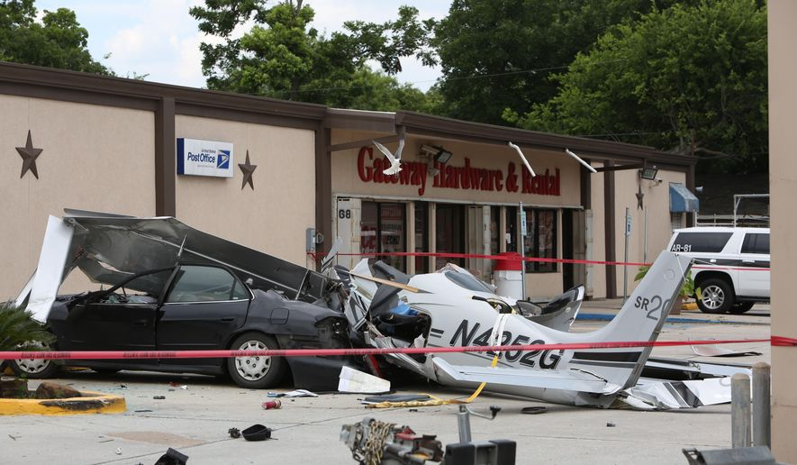 A small plane that crashed into a car in a parking lot near a Houston airport is roped off on Thursday, June 9, 2016. The  aircraft had been trying to land at Hobby Airport, in the southeastern part of the city,  when it crashed less than a mile northwest of the airport, said Lynn Lunsford, a spokesman for the Federal Aviation Administration.   (Steve Gonzales/Houston Chronicle via AP) MANDATORY CREDIT