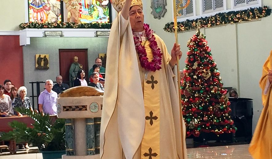 This Jan. 4, 2015 photo shows Archbishop Savio Tai Fai Hon blessing the audience at Dulce Nombre de Maria Cathedral-Basilica in Hagatna, Guam. Hon is the Vatican administrator appointed to temporarily oversee the Catholic church in Guam while an investigation is underway into allegations that Archbishop Anthony Apuron sexually assaulted young boys over several decades. Pope Francis appointed Hon on Monday, June 6, 2016 to take over the Agana archdiocese, and he is expected to remain on Guam until the Holy Father deems the church in Guam is stable. (AP Photo/Grace Garces Bordallo)