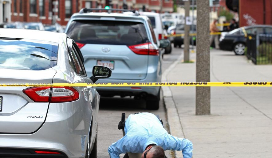 An investigator checks under a car at the scene of a multiple shooting  outside the Jeremiah E. Burke High School, in Boston's Dorchester neighborhood, Wednesday, June 8, 2016.  Police are searching for a suspect in the brazen daylight shooting that left one student dead and three other people wounded. (Angela Rowlings/Boston Herald via AP)