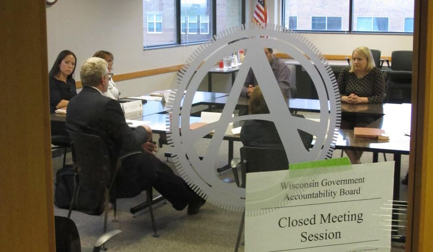Members of the newly created Wisconsin Ethics Commission meet in closed session with staff of the Government Accountability Board on Thursday, June 9, 2016, in Madison, Wisc. The new partisan Ethics Commission, and one focused on elections, will replace the nonpartisan GAB on June 30, requiring a reorganization and removal of the old logo from the meeting room door. (AP Photo/Scott Bauer)