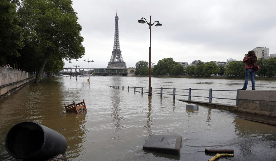 In this June 4, 2016, file photo, a woman, at right, takes photos of the flooded banks of the Seine river in Paris. An international team of scientists has found that man-made climate change nearly doubled the likelihood of last month's devastating French flooding. In a quick but not peer-reviewed analysis, the World Weather Attribution team of climate scientists used past rainfall data and computer simulations to look for global warming's fingerprints in the heavy downpours in France and Germany. (AP Photo/Francois Mori)