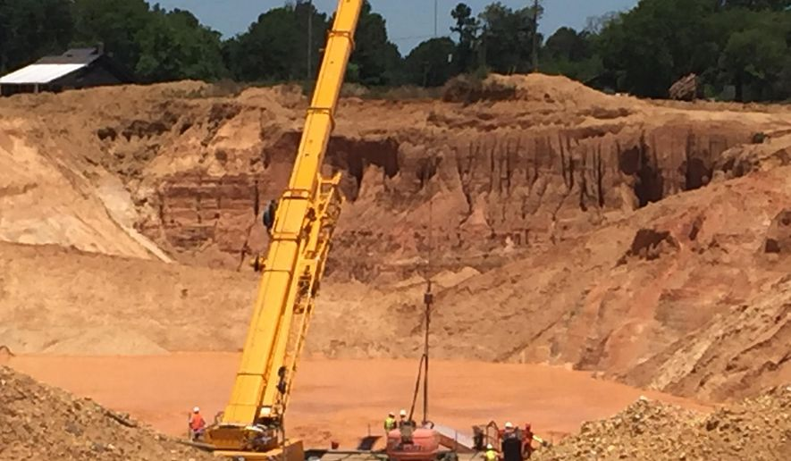 In this photo released by the Mississippi Emergency Management Agency, a new crane is used to assist in the recovery efforts to remove two workers buried under a landslide at the bottom of a pit at Green Brothers Gravel Co., in Crystal Springs, Miss., Tuesday, June 7, 2016.  (Ray Coleman/Mississippi Emergency Management Agency via AP)