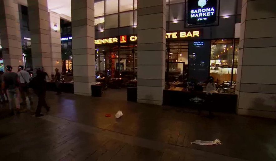 This video still image taken from APTN shows the scene of a shooting in central Tel Aviv, Israel on Wednesday, June 8,  2016.  Two Palestinian gunmen opened fire at bystanders near the popular open-air market on Wednesday night before being detained, Israel police said. (AP Photo/APTN)