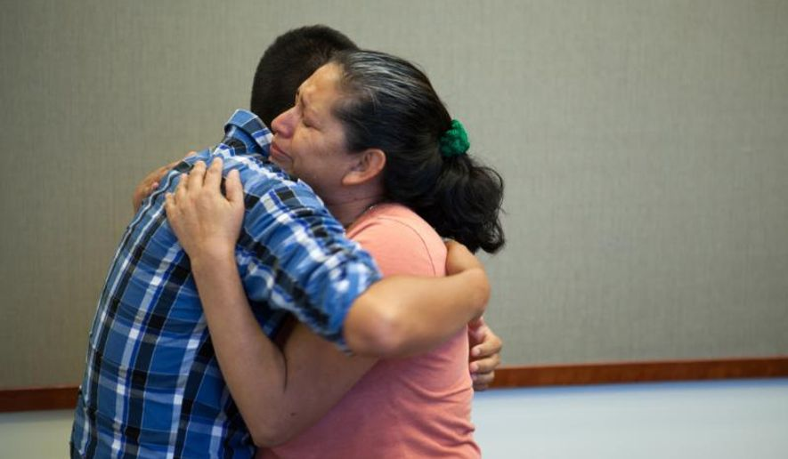 Steve Hernandez wipes a tear from his mother's eye after seeing her for the first time in 20 years in San Diego, Calif., on Thursday, June 9, 2016. Steve Hernandez was abducted by his father Valentin Hernandez from their Rancho Cucamonga residence in 1995 when he was 18-months-old. Since that time, 42-year-old Maria Mancia had searched for her son to no avail. The boy, Steve Hernandez, now a man of about 22, has been found in Mexico. On Thursday he was brought to the U.S. to meet his mother.Authorities interviewed the boy and took a DNA swab. The facts of his life, and the DNA, matched. (Christopher Lee/San Bernardino County District Attorney's Office via AP)