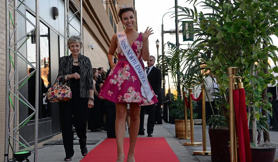 "In this photo taken Wednesday, June 8, 2016, Miss North Dakota Delanie Weidrich makes her way down the red carpet at the premiere of the movie ""Woodlawn: in Williston, N.D. (Elizabeth Hackenburg/Williston Herald via AP) MANDATORY CREDIT"
