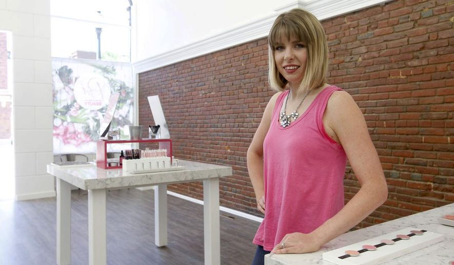 In this June 7, 2016 photo, Krista Dolash, founder and owner of Root, poses in the store in downtown Cedar Falls, Iowa. Dolash wants to change the color of the front of her building to pink. (Tiffany Rushing/The Courier via AP) MANDATORY CREDIT