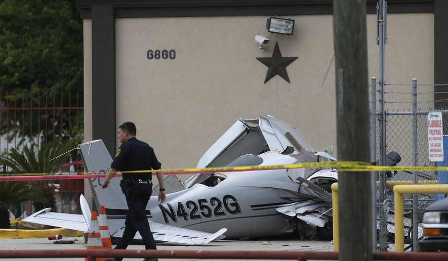 Authorities investigate the scene where a small plane crashed into a car in a parking lot near a Houston airport on Thursday, June 9, 2016. The  aircraft had been trying to land at Hobby Airport, in the southeastern part of the city,  when it crashed less than a mile northwest of the airport, said Lynn Lunsford, a spokesman for the Federal Aviation Administration.   (Mark Mulligan/Houston Chronicle via AP) MANDATORY CREDIT