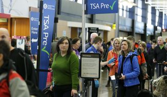 FILE - In this March 17, 2016, file photo, travelers authorized to use the Transportation Security Administration's PreCheck expedited security line at Seattle-Tacoma International Airport in Seattle have their documents checked by TSA workers. Massive lines at airports have now led to a backlog of people trying to enroll in trusted traveler programs. Waits to join PreCheck or Global Entry are months long in some cities. (AP Photo/Ted S. Warren, File)