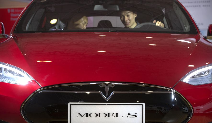 FILE - In this Monday, April 25, 2016, file photo, a man sits behind the steering wheel of a Tesla Model S electric car on display at the Beijing International Automotive Exhibition in Beijing. Tesla said Thursday, June 9, 2016, that it has started selling a cheaper version of its Model S car in an attempt to make its electric vehicles more affordable for more people. The new version, called the Model S 60, starts at $66,000. An all-wheel drive version of the Model S 60 will start at $71,000. Both cost less that the current Model S 90D, which starts at $89,500. (AP Photo/Mark Schiefelbein, File)