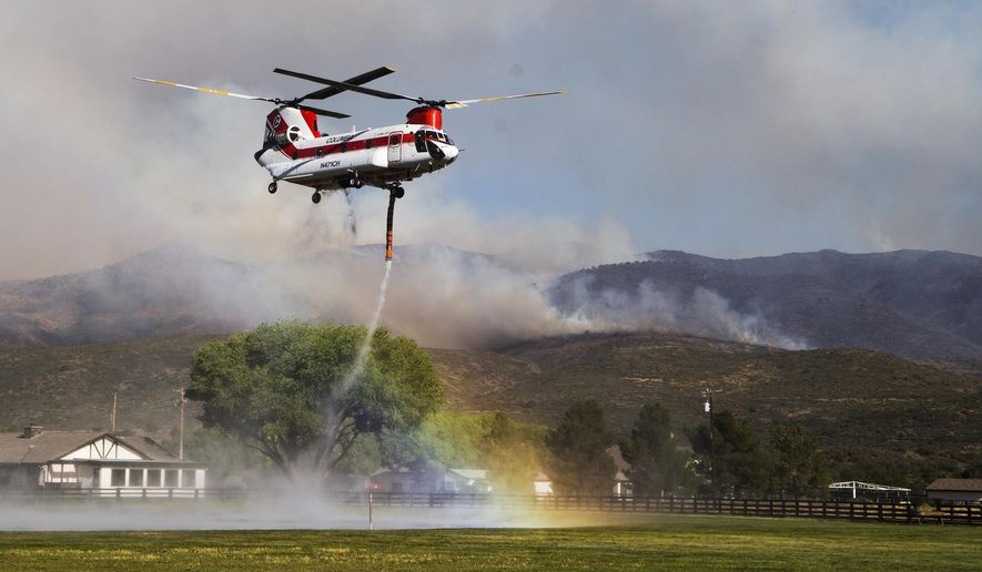 A rainbow forms as a helicopter picks up water to drop on the Tenderfoot Fire near Peeples Valley, Ariz., Thursday, June 9, 2016. A brush fire that began Wednesday pushed evacuations to several hundred as more people fled homes Thursday near Yarnell, an Arizona community. Authorities ordered additional evacuations Thursday, including homes in the Peeples Valley Area, as they feared the fire might make its way down to Highway 89. (Tom Tingle/The Arizona Republic via AP)  MARICOPA COUNTY OUT; MAGS OUT; NO SALES; MANDATORY CREDIT