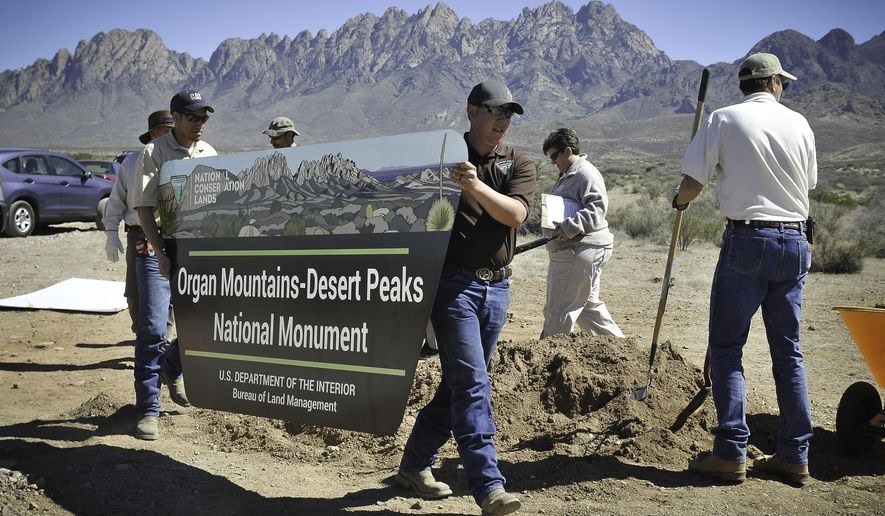 FILE - In this March 15, 2015 file photo, a sign is installed at the new Organ Mountain-Desert Peaks National Monument in Las Cruces, N.M. Almost a half-million acres in southern New Mexico were designed as a national monument two years ago, and now members of the state's congressional delegation are pushing for portions of the Organ Mountains-Desert Peaks area to be set aside as wilderness. (Jett Loe/AP Photo/Las Cruces Sun-News via AP, File)