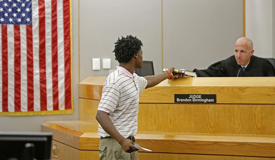 Johnathan Monroe , left, gives the Autobiography of Martin Luther King, Jr., back to Judge Brandon Birmingham at Frank Crowley Courts Building on Monday, June 6, 2016, in Dallas.   Monroe participates in the Achieve Inspire Motivate (AIM) program, which allows young, non-violent felony offenders between the ages of 18 and 25 to get their criminal cases dismissed and records expunged after completing the program. (Jae S. Lee/The Dallas Morning News via AP) MANDATORY CREDIT; MAGS OUT; TV OUT; INTERNET USE BY AP MEMBERS ONLY; NO SALES