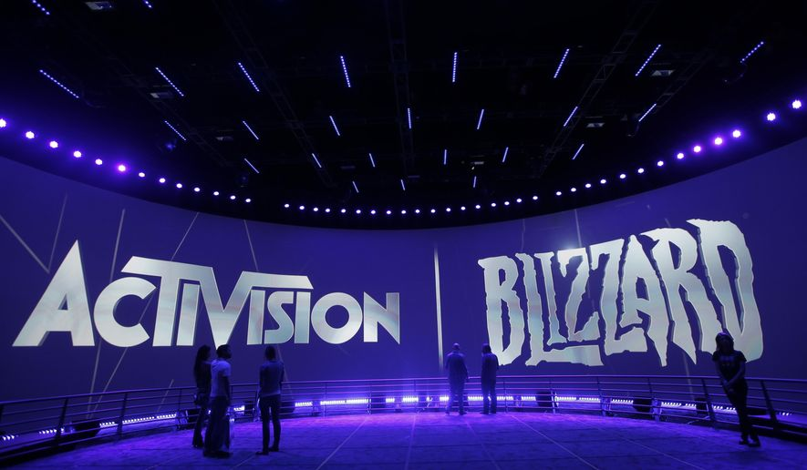 FILE - In this June 13, 2013 file photo, people view the Activision Blizzard Booth during the Electronic Entertainment Expo in Los Angeles. Electronic Arts and Activision are among the video game publishers angling to cut through the noise on the Electronic Entertainment Expo show floor by ditching their long-standing E3 booths in favor of low-key, fan-focused events. (AP Photo/Jae C. Hong, File)