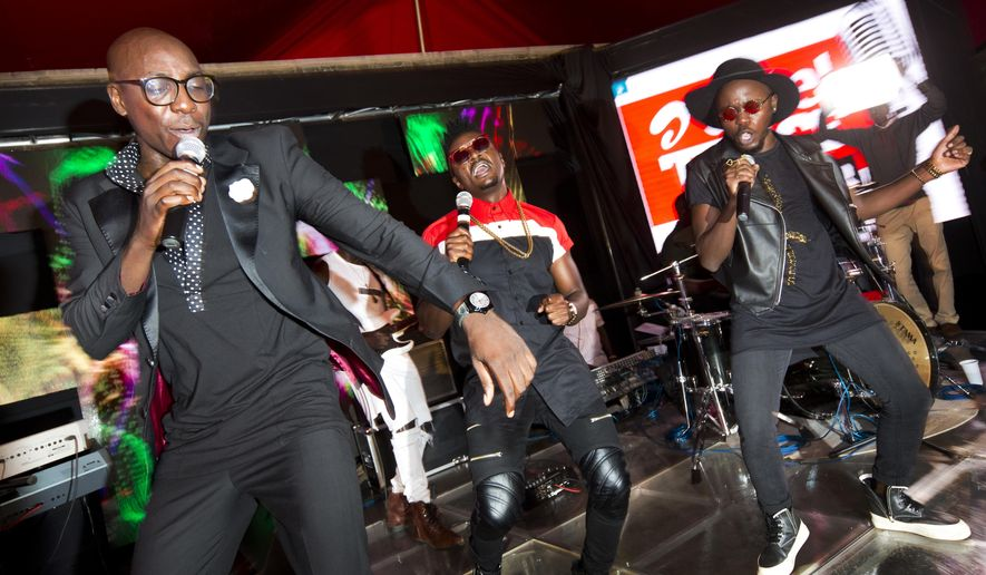 In this photo taken Wednesday, April 6, 2016, members of the Kenyan music group Sauti Sol, from left to right, Bien-Aime Baraza, Savara Mudigi, and Willis Austin Chimano, perform at an event in Nairobi, Kenya. Not many musicians can boast they've made President Barack Obama get up and groove to their tunes but Kenyan band Sauti Sol did just that with their mix of Afro-pop, soul and R&B, which has won a number of international awards. (AP Photo/Ben Curtis)